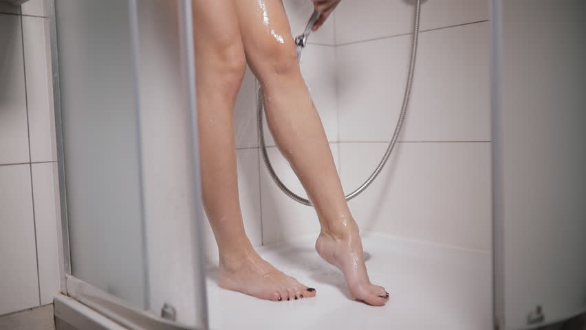 Woman shave her legs with razor in shower cabin