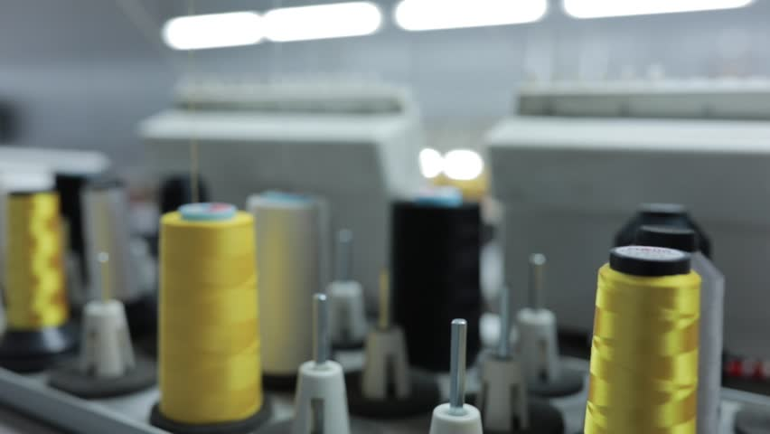 Rows of spools of thread of different colors in the industrial sewing machine. Different parts of the sewing machine. Yarn tensioning system in the sewing equipment | Shutterstock HD Video #33334093