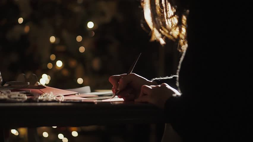 Girl writes a pen, a caligraphic handwriting, in a New Year's atmosphere a letter to her beloved. Sitting at a table with candles, next to decorated New Year trees, waiting for Christmas. 2019