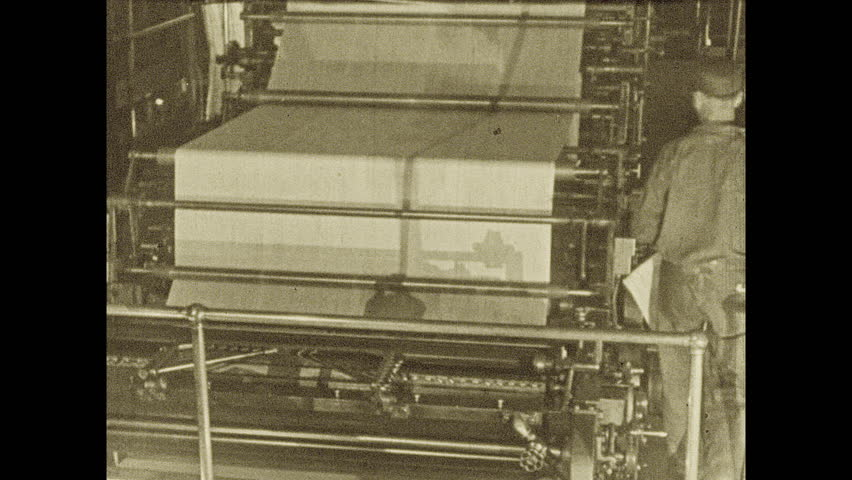 1920s: UNITED STATES: paper on printing press. Man reads paper by machine. Man sells newspapers from stand on street