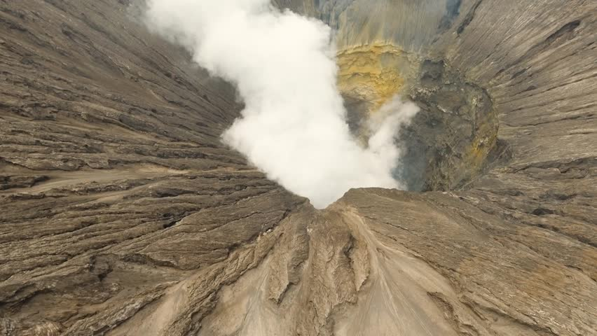 Flight over the active crater of the volcano, white smoke. Aerial view of volcano crater Mount Gunung Bromo is an active volcano,Tengger Semeru National Park. 4K video. Aerial footage.