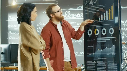 Female Developer and Male Manager Use Interactive Whiteboard Presentation Touchcreen to Look at Charts, Graphs and Growth Statistics. They Work in the Stylish Creative Studio. Shot on RED EPIC-W 8K