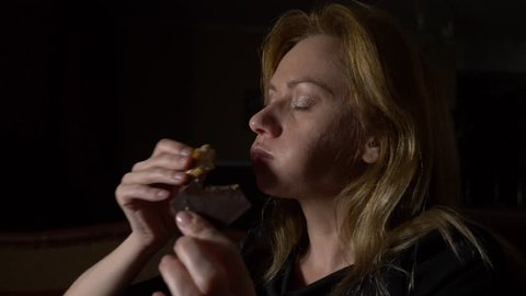 woman at night eating buns. concept of an eating disorder. 4k, slow motion