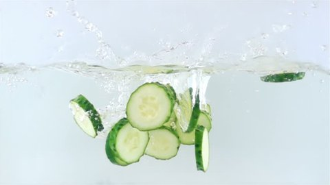 Slow Motion Video of Sliced Cucumber Piaces Falling in Water with Splash