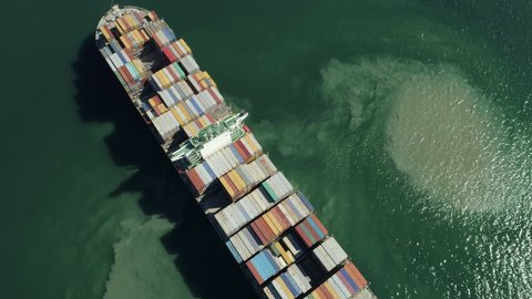 AERIAL TOP DOWN: Flying over massive container ship filled with multicolored containers moving in the quiet sea. Colorful containers being moved by large international cargo ship to final destination.