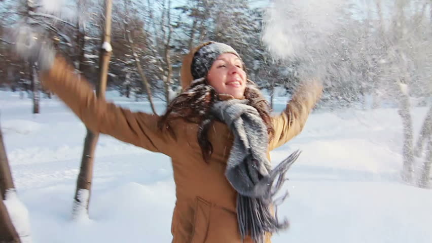 SLOW: Girl in a park is happy about throwing snow