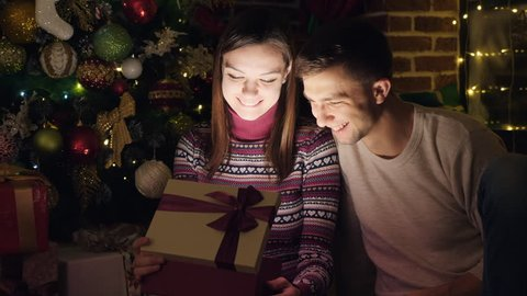 A Christmas gift. A man and a woman open a box with a gift. Bright light from the box. Christmas, New Year.