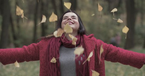 Young woman tossing up leaves in autumn forest park 4k slow-motion video. Overweight fat female playing, leaves falling.