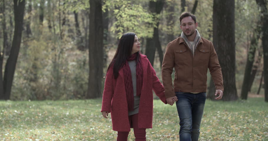 Loving couple walking in autumn forest park 4k slow motion video. Young man and overweight fat woman speaking romantic date. Love story romance concept