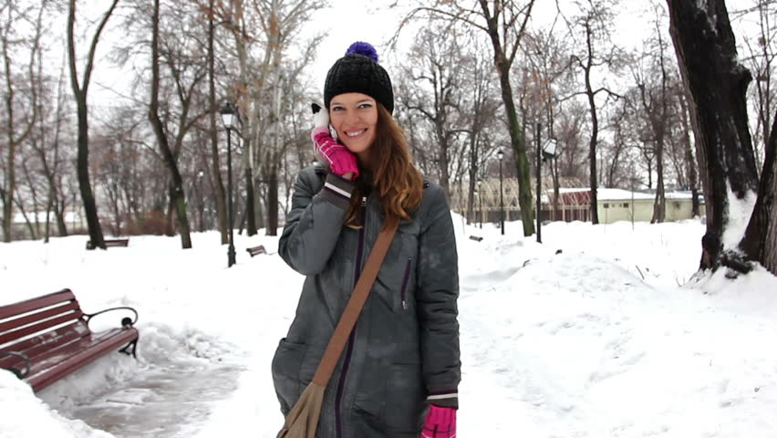 young nice girl speaks by mobile phone in winter park.