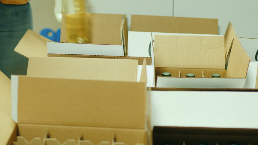 Two workers in the winery put bottles of wine in boxes. Preparing for shipment to consumers #33442123