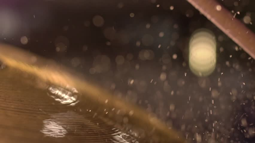 Drummer hitting on wet drum cymbal, and the water splashing from cymbal in slow motion 120 fps.