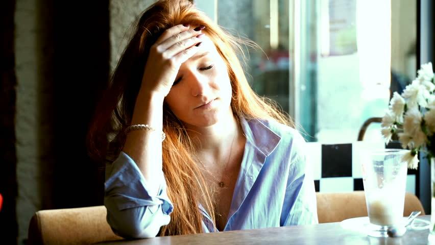 Young, pretty woman having headache in cafe | Shutterstock HD Video #33476983