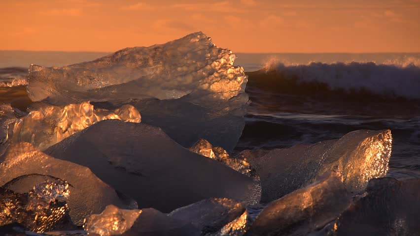 Winter sunrise light with diamond ice - waves splashes and iceberg in the ocean