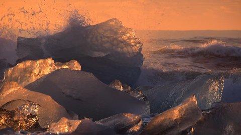 Winter sunrise light with diamond ice - waves splashes and iceberg in the ocean