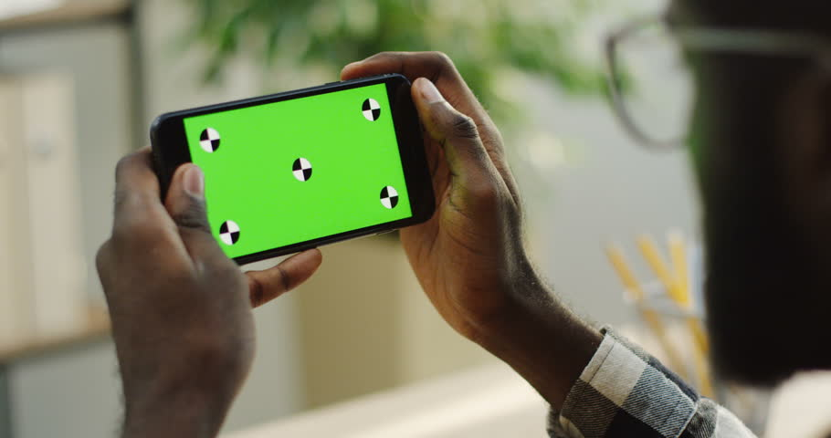 Over shoulder view on the African American male hands holding black smartphone horizontally and taping on it on the blurred room background. close up. Green screen. Chroma key. Tracking motion #33502933