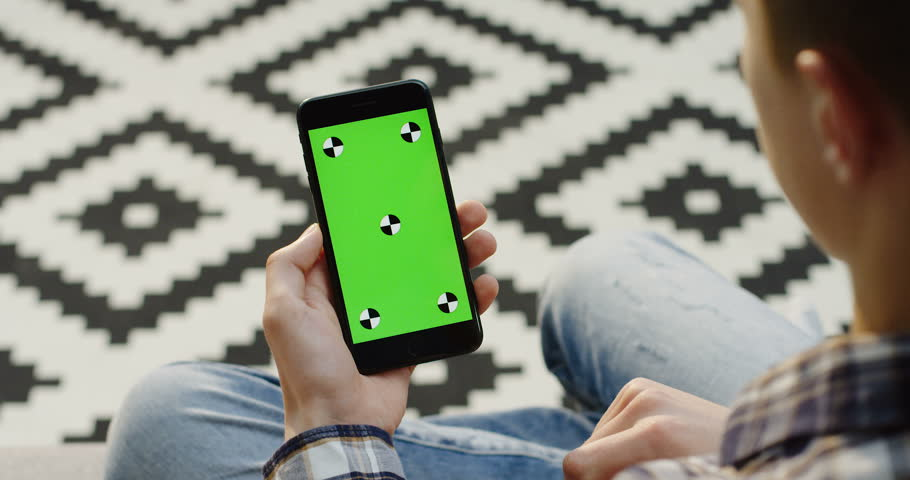 Black smartphone with green screen and tracking motion in the hands of caucasian man. Vertically. Fingers scrolling, zooming and taping on it. Blurred patterned floor background. Close up. Chroma key.   Shutterstock HD Video #33503023