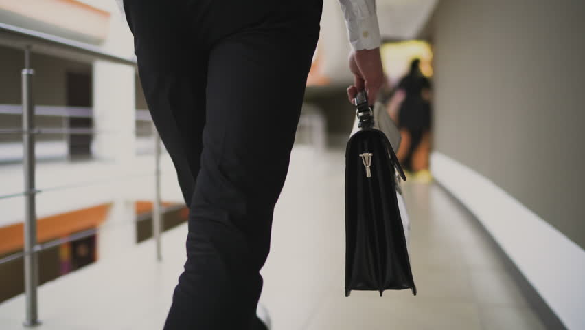 Businessman with briefcase walking across the office building. Close up. 4K | Shutterstock HD Video #33511423