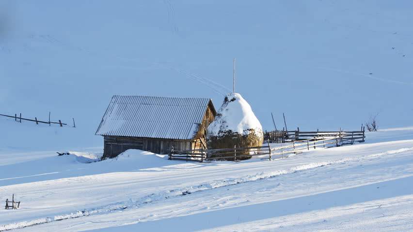 Small rural household covered with snow