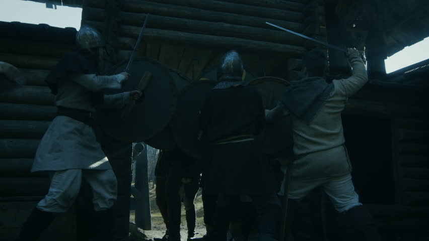 Medieval Battle. Viking Warriors Break into Wooden Fortress Yard and Fight with Slavs Guards. Violent Fight with Swords, Axes and Shields. Slow Motion. Medieval Reenactment. Shot on RED EPIC-W 8K.