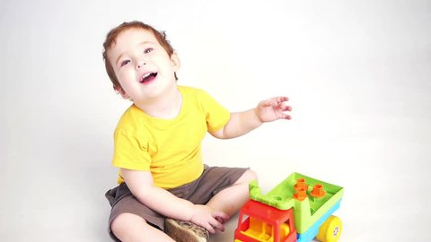 a child playing with a toy truck smiling