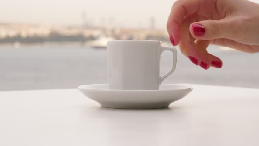 Tourist woman enjoy traditional hot Turkish drink at panoramic terrace, hand take small cup of coffee, nice blurred background, silhouetted Bosphorus Strait panorama. Lady take gulp and place cup back