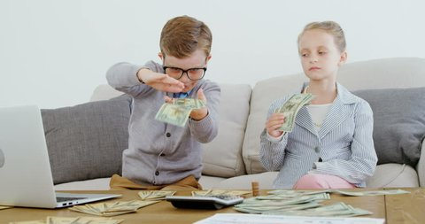 Kids as business executive throwing money in office 4k