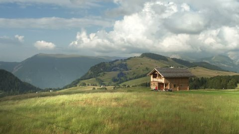 Hayfield in alpine mountains landscape with wooden chalet aerial view