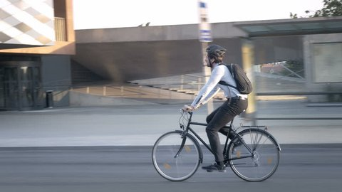Businessman wearing formal clothes riding a bike on his commute. Elegant handsome young professional travelling to job on a bicycle on the street in the city.