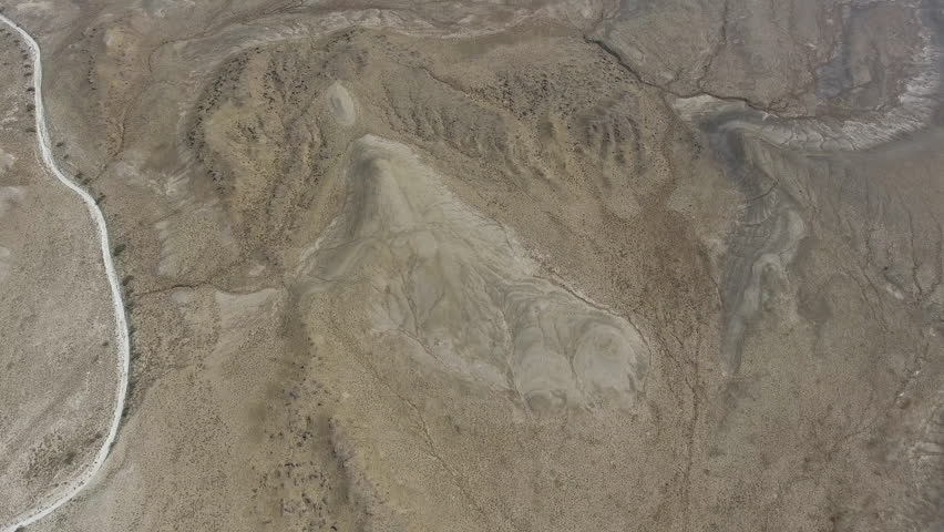 A view of the soil surface and rivulets of liquid mud of clay birds eye view of landscape with high hills and canyons in desert landsaerial video sciox Images