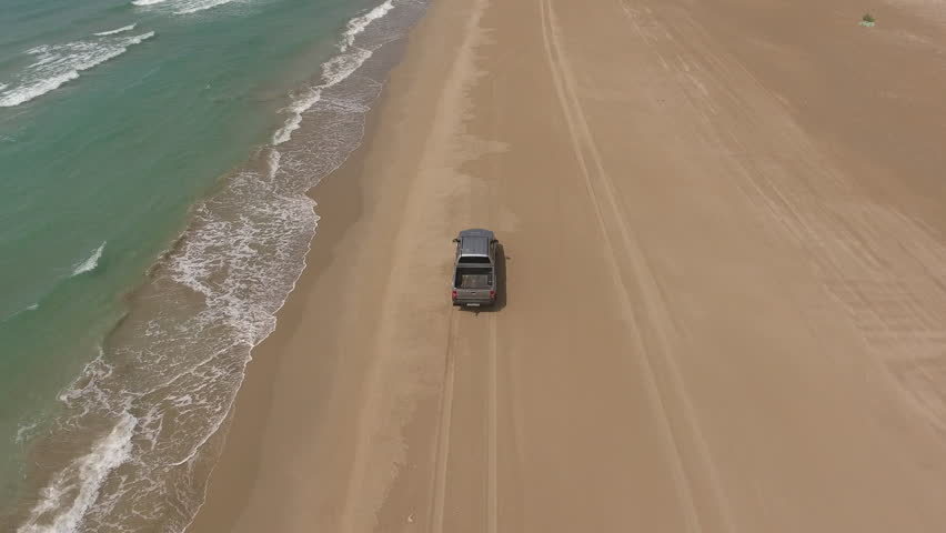 Bird's view of rented car with tourists enjoying environment in summer time during extreme ride along seashore.Video of leased automobile driving on dry coastline of island during expedition