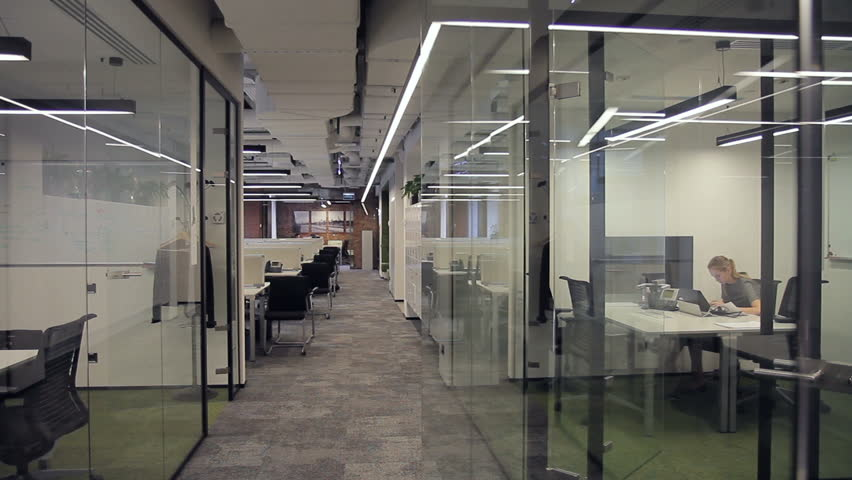 Business center with offices with glass partitions, in which employees work. Representations of different companies and companies are located in a spacious, bright and modern room.
