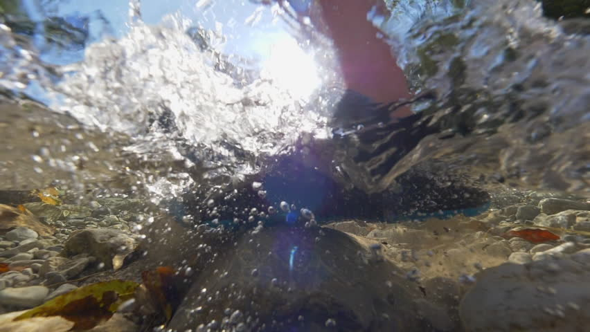 HALF-HALF, LENS FLARE: Unknown trekker walks across a shallow forest stream. Clear water splashing and bubbling as unrecognizable person sets foot into cold river water running down a rocky riverbed.