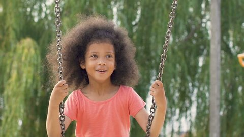 Lovely mixed-race girl with curly hair swinging with great enthusiasm, slow-mo