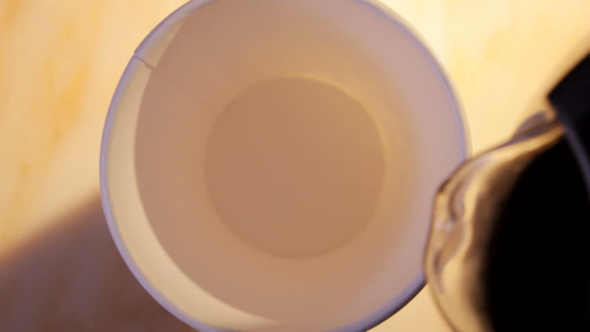 Close up HD video of coffee and milk pouring into paper cup, hand takes cup away from right side. | Shutterstock HD Video #3369689