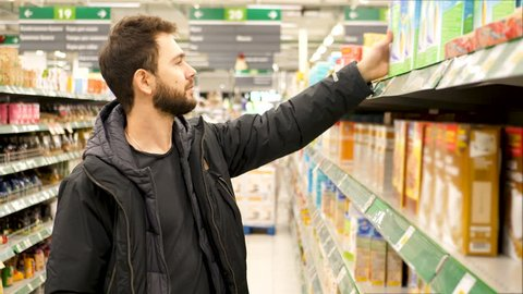 Man checking food labelling in supermarket. 4K UHD