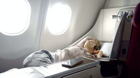 young pretty girl is a passenger of a first class in airplane, is lying on a bed during voyage