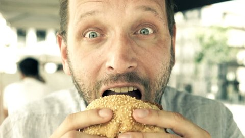 Hungry, funny man eating burger in city cafe