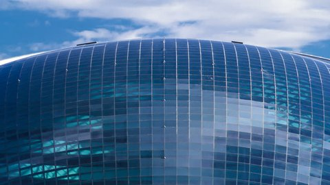 ASTANA, KAZAKHSTAN - CIRCA JULY 2016: Nazarbayev Center and blue tower, with clouds ond reflection on blue glass. Close up view from bridge. Cloudy sky. Astana, Kazakhstan