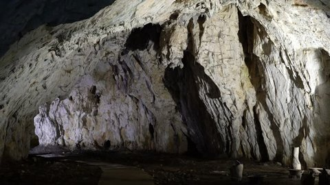 Interior of a cave with cave formations like stalactites and stalagmites. Establishing shot.