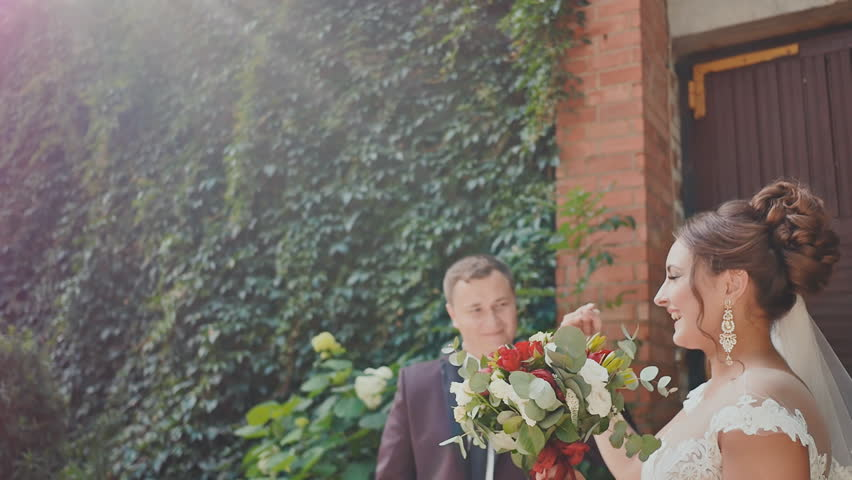 The newlyweds joyously dance at the brick wall with growing branches of grapes. The groom in the dance kisses his bride with a bright bouquet in his hands. A touching moment for a wedding day. | Shutterstock HD Video #33769267