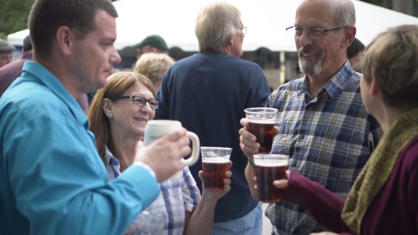 Friends of mixed ages stand around, laugh and talk while holding and drinking dark beer. #33776713