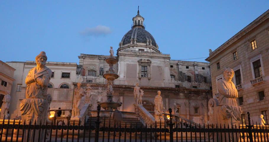 Palermo, Sicily, Italy. Dec 08 2017: Pretoria Fountain of Palermo, fountain of white marble with people and low lights of sunset. Ita: Fontana Pretoria di Palermo, Fontana della Vergogna