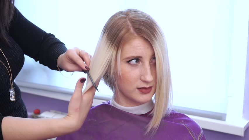Woman getting new haircut by hairdresser at beauty salon. polishing hair. haircut is completed, the result shows the hairdresser