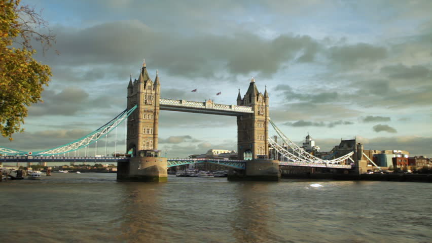 Distant slow motion view of Tower Bridge on Thames River in London, England.