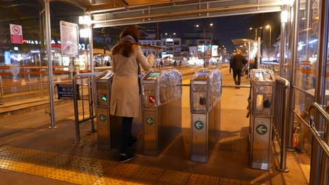 Woman (model released) use contactless payment with Istanbul transport card, walk through turnstile to tram station platform at night time. Four gates packed with plastic to protect from weather