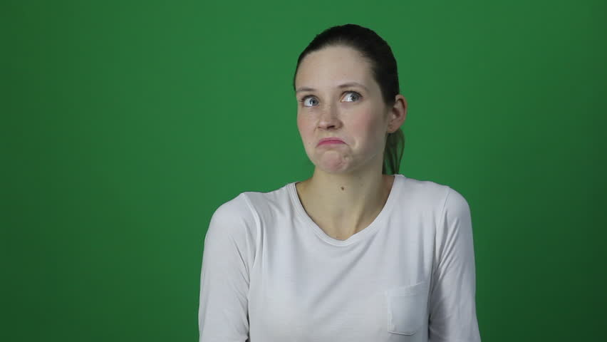 What? I don't know. Puzzled woman looking at camera. Studio shot, isolated in light green background