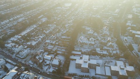 Aerial View of Houses in England on a Snowy Morning With Rooftops Covered in Snow and Cars Driving Along the Icy Roads