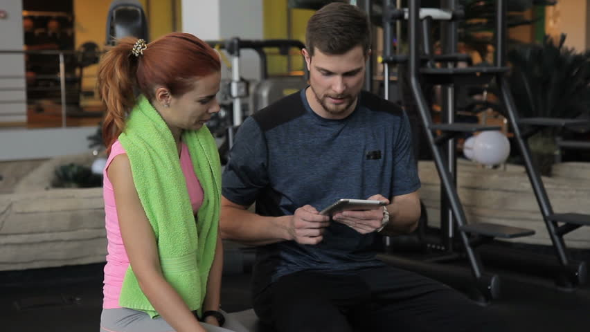 The male trainer is counting the results of his female client on his tablet in the gym. The man in dark grey t-shirt stands with the woman in pink sleevless shirt and with green towel and asks her | Shutterstock HD Video #33862363