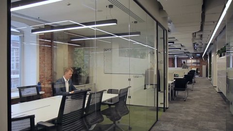 Business staff are working in spacious office with glass partitions. In bright room with transparent walls are busy with their own business man in a suit and other people.